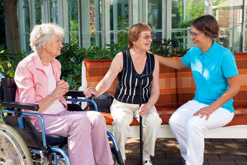 Two old women sitting chatting on a garden bench supported by a
