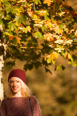 Young woman under autumn leaves tree