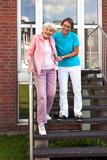 Friendly carer helping a senior lady on steps.