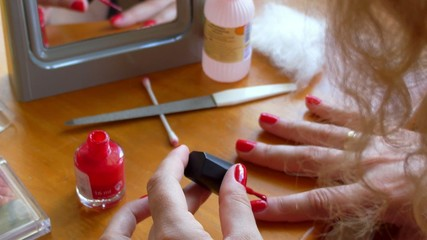 Woman Applying Red Nail Polish to Hand. Home Manicure.