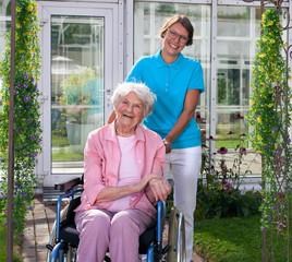 Professional carer behind happy elderly woman.