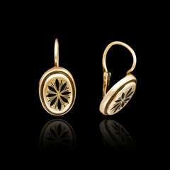 Gold earrings isolated on black background