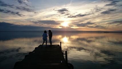 Familia en muelle durante la puesta de sol