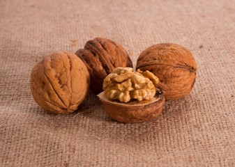 Walnut kernels and whole walnuts on texture background
