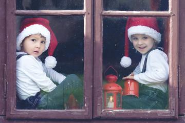 Two cute boys, looking through a window, waiting for Santa