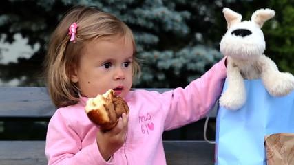 Little girl eating a bun.