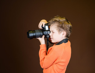 Child in studio with professional camera. Boy using camera.