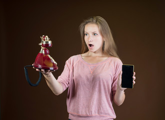 Girl with conventional telephone and smartphone in her hands.