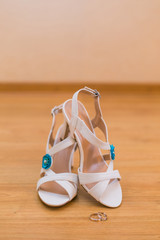 Close up of bride's shoes and gold rings
