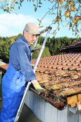 Mann auf Leiter säubert Dachrinne von Laub