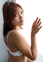 melancholic girl standing beside the window.