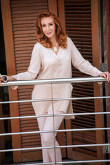 adult beautiful red-haired woman standing on the balcony