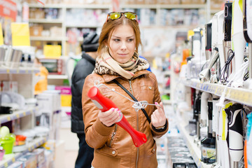 beautiful woman in a supermarket chooses blender