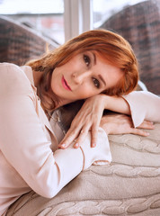 adult beautiful red-haired woman lying on a couch