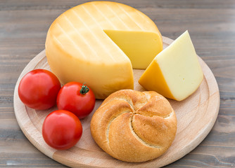 Smoked cheese wheel, tomatoes and bread on wooden table