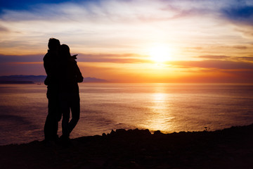 Couple looking the sunset and ocean