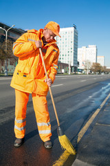 Road sweeper cleaning city street with broom tool