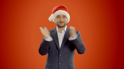 young businessman dancing in a hat santa claus