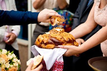 жених отламывает свадебный каравай