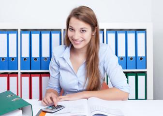 Lachende Studentin mit Taschenrechner