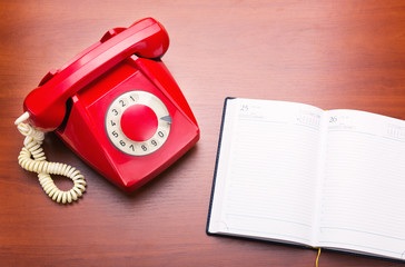 Red retro telephone with notebook