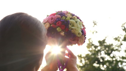 Girl with bunch of flowers in the sunlight.