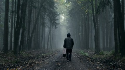Man in coat with old suitcase in a foggy, ghostly autumn forest