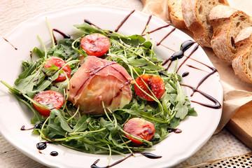 Mozzarella baked in ham of Parma with arugula