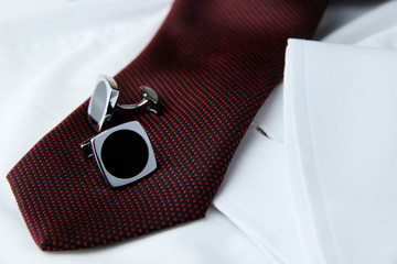 A pair of cuff links on a brown cravat on the white shirt