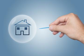 Hand mit einer Nadel zersticht Blase mit einem Haus