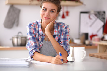 Smiling woman with cup of coffee and newspaper in the kitchen