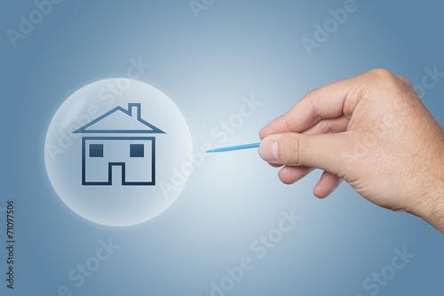 Leinwandbild Motiv Hand mit einer Nadel zersticht Blase mit einem Haus