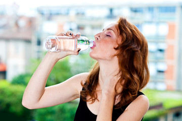 freckled woman drinks water from bottle