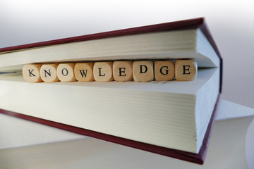 Knowledge message written in wooden blocks between pages of a bo