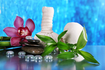 Spa composition with herbal massage bags, orchid and bamboo