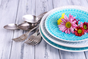 Plates and vintage cutlery on color wooden background