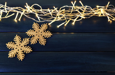 Garland and snowflakes on dark wooden background