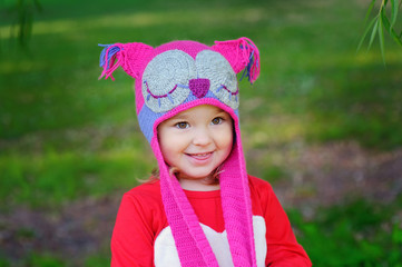 Cute little girl on the meadow in summer day a knitted hat owl