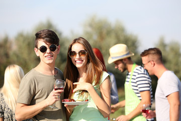 Young couple with friends on rest, outdoors