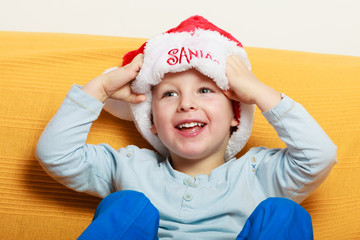 little boy in red santa hat sitting on couch at home