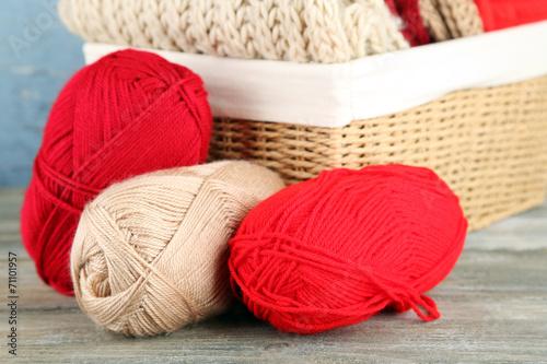 Leinwandbild Motiv Knitting clothes and yarn in basket, on wooden background