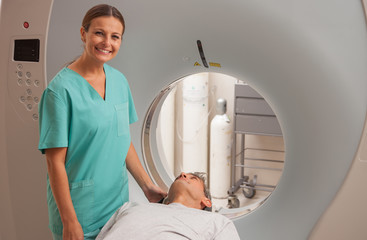 Man undergoing magnetic resonance with reassuring female doctor