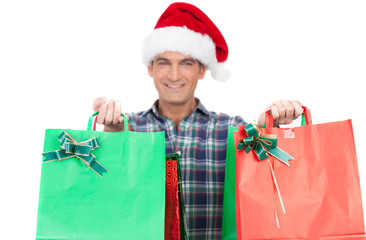 Happy man with Santa red hat holding Christmas bags. Isolated on