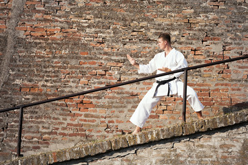 Man practicing martial arts in old town