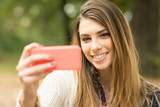 Young woman taking a selfie outdoors in autumn. No retouch poster