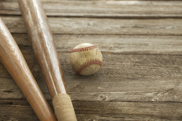 Old baseball and bats on rough wood surface