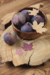 Wooden bowl with ripe fig fruits and maple leaves, vertical shot