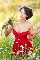 Young voluptuous brunette holding a wild flowers bouquet