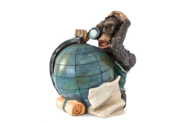 The figurine of a monkey considers the globe
