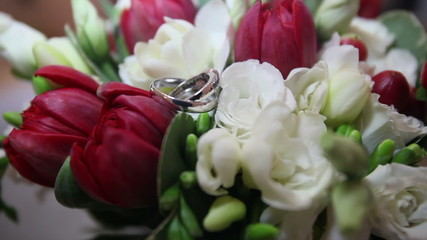 bouquet of red and white roses lays wedding rings